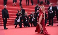 Uzmanības kāra modele uz sarkanā paklāja gozējas ar pliku dupsi