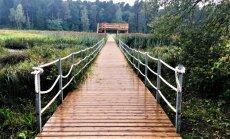 Skatu platforma un laipa, kas šķērso ezeru: pastaigu taka Kazdangā