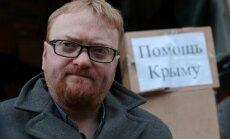 Sanktpēterburgas deputāts demonstratīvi iemet Ukrainas karogu atkritumu urnā