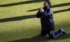 Argentina s soccer team coach Diego Maradona kneels while speaking to a journalist