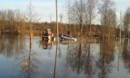 """ФОТО, ВИДЕО: В Латгалии на затопленной дороге """"утонул"""" Volvo"""