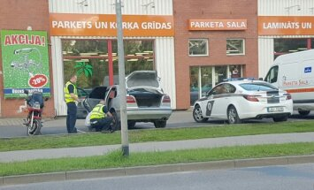 Foto: Izpalīdzīgi policisti palīdz sievietei nomainīt automašīnas riepu