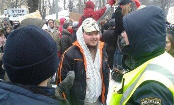 Pie valdības mājas aiztur vienu no protestētājiem pret ACTA
