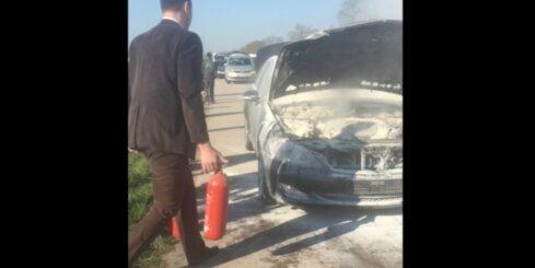 Vairāki cilvēki Jelgavas šosejas malā dzēš degošu 'Mercedes' auto