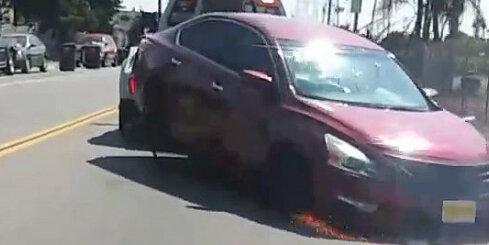 Evakuators ASV turpina vilkt auto, kuru īpašnieks mēģina atāķēt