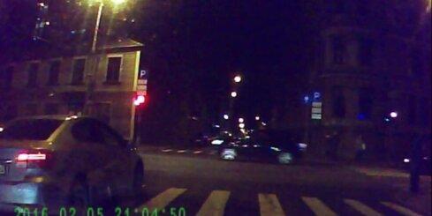 Pie sarkanā luksofora signāla aizjož divi gājēji un auto