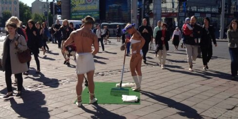 Pusplika meitene un zēns pie Rīgas stacijas 'pļauj zāli'