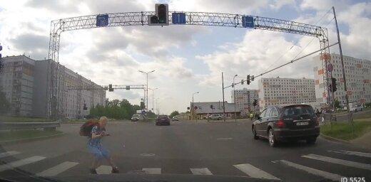Video: Skolnieks skrien pie sarkanās gaismas un gandrīz paskrien zem auto