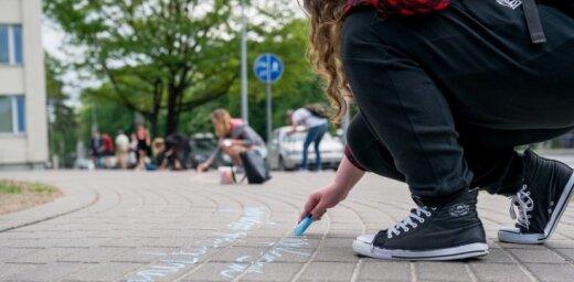 Foto: Jaunieši Jūrmalā uz asfalta raksta Raiņa un Aspazijas dzeju