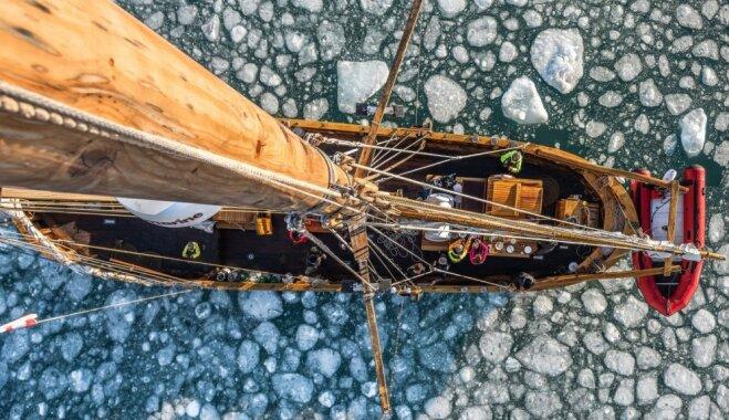 Dienas ceļojumu foto: Laiviņa dreifē cauri milzīgam aisbergam