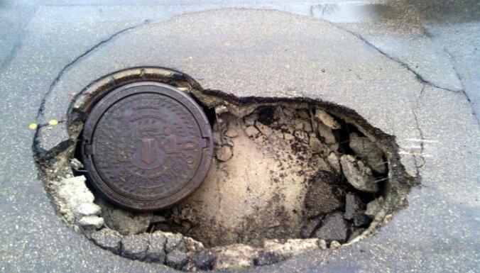 ФОТО: В Лиепае под пассажирским автобусом провалился асфальт, транспорт застрял в яме