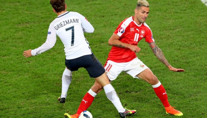 Switzerland s Valon Behrami fights for the ball against France s Antoine Griezmann
