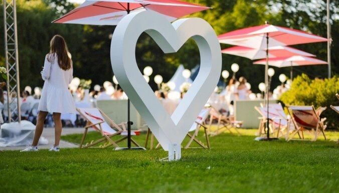 Foto: Kupls baltā tērptu ļaužu pulks eleganti pikniko Rīgas centrā