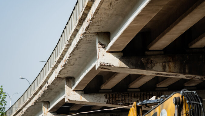 """Рижане возмущены: дорожные рабочие """"живут"""" под Калнциемским мостом и мешают спать по ночам"""