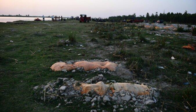 Indijā upes krastos seklos kapos atrasti simtiem cilvēku līķu