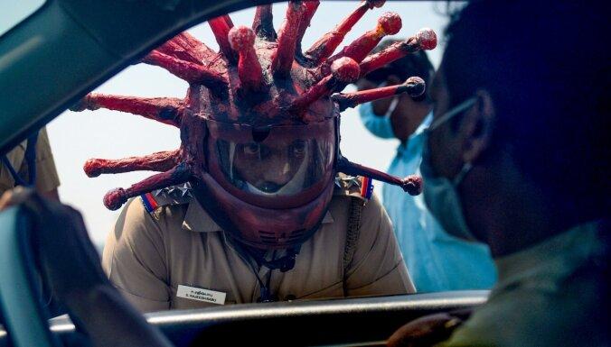 Foto: Indijā ļaudis biedē policists koronavīrusa ķiverē