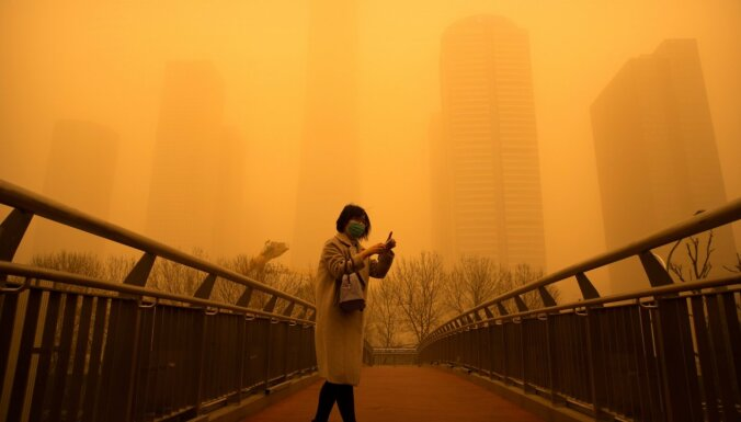 Foto: Smilšu vētra pārkrāso Pekinas debesis oranžos toņos