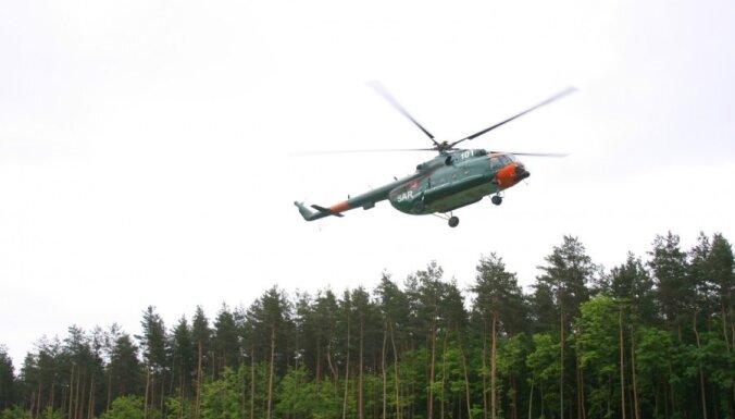 Vērienīga kūlas ugunsgrēka dzēšanā Kurzemē nejauši iesaistās NBS helikopters