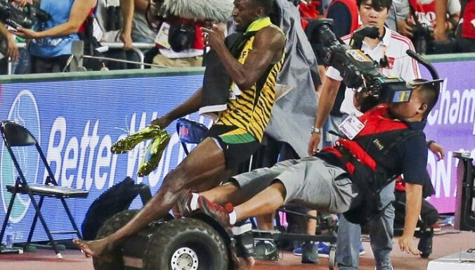 Usain Bolt of Jamaica is hit by a cameraman on a Segway