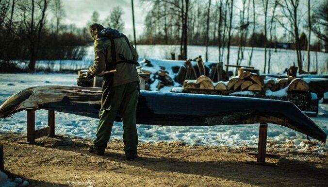 Līgatnieši pašu rokām radītā vienkoča laivā bauda Gaujas straujos ūdeņus janvārī