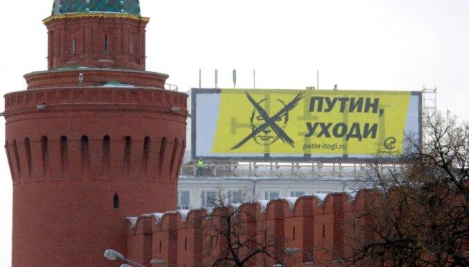Pie Kremļa izkar plakātu ar uzrakstu 'Putin, aizej!'