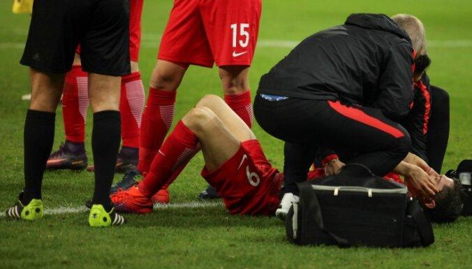 Poland Robert Lewandowski receives medical assistance after fire cracker