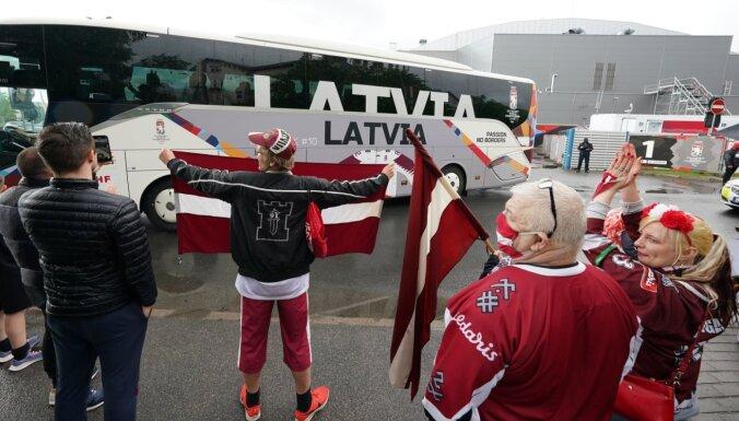 Foto: Kopā priekos un bēdās - Latvijas fani uzmundrina hokejistus pēc zaudējuma