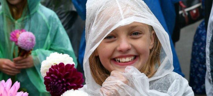 Foto: Smaidīgi ļaudis lietū svin Rīgas svētkus