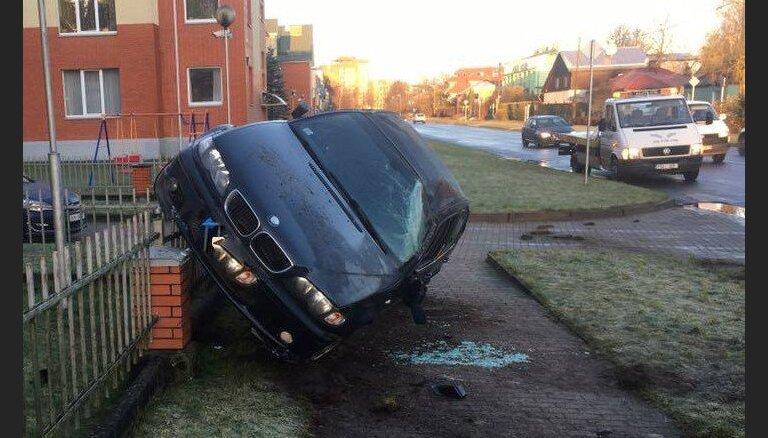 ФОТО: На Югле автомобиль BMW перевернулся и повис на заборе