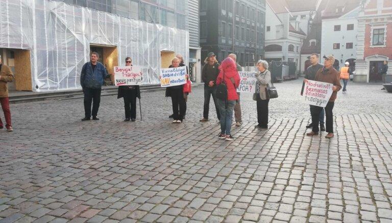 Rīgas domes deputātus pirms pirmās sēdes pie Rātsnama sagaida daži piketētāji