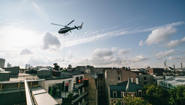 ФОТО. Вертолет и кран: в тихом центре Риги летали деревья
