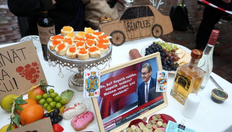 Бутерброды с икрой и портрет Бондарса: протестующие накрыли стол возле здания Сейма